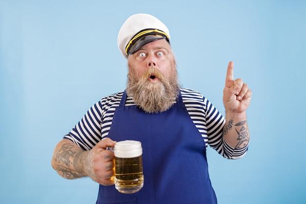 太りすぎの感情的な船乗りは、水色の背景にビールとジェスチャーを保持します