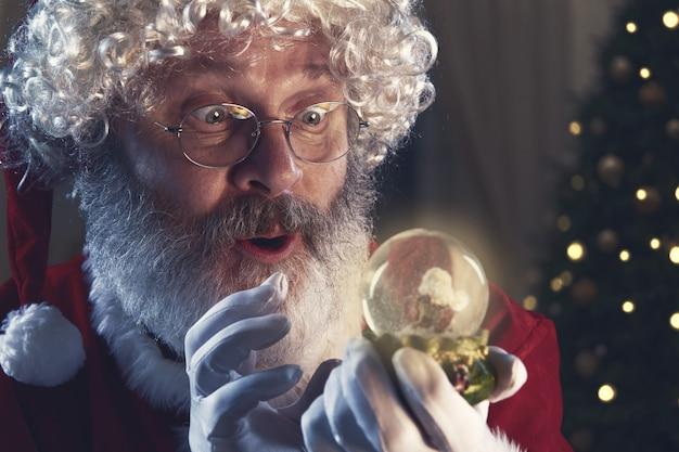 Эмоциональный дед мороз поздравляет с новым 2020 годом и рождеством. человек в традиционном костюме держит шар волшебной сферы с елкой на backgorund. зима, праздники, распродажи. copyspace.