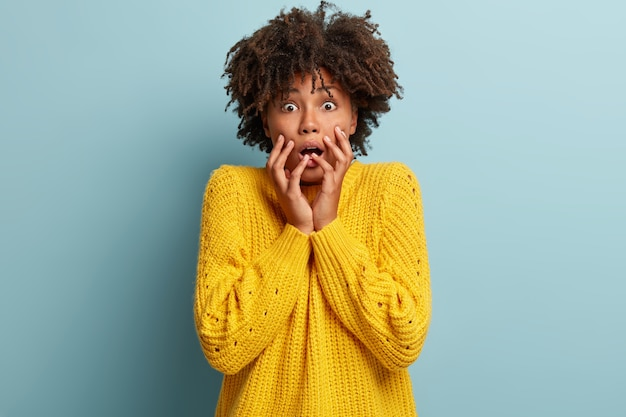 Emotional scared afro american lady stares with bated breath, feels intense, holds hands near face, has bugged eyes, being insecure, dressed in yellow jumper, stands indoor. negative emotions