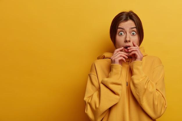 感情的に怖がっている心配している女性は、カメラを非常に恐れて見て、彼女の目を信じることができず、息を止め、黄色のスウェットシャツを着ています