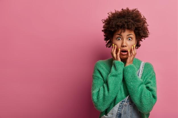 Donna spaventata emotiva che è in preda al panico, afferra il viso e fissa con gli occhi spalancati, è allarmata e spaventata, mantiene la mascella aperta, ha difficoltà, indossa un maglione verde, modelle su un muro roseo