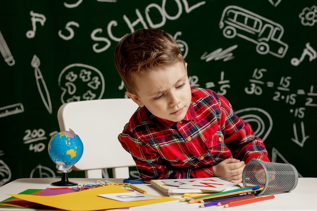 多くの学用品を机の上に座っている感情的な学校の男の子。学校の最初の日。小学校の子供男の子。学校に戻る。小学校の子。
