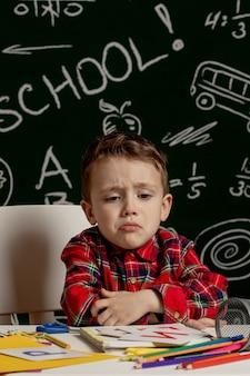 Эмоциональный школьник сидя на столе с много школьных принадлежностей. первый день в школе. малыш мальчик из начальной школы.