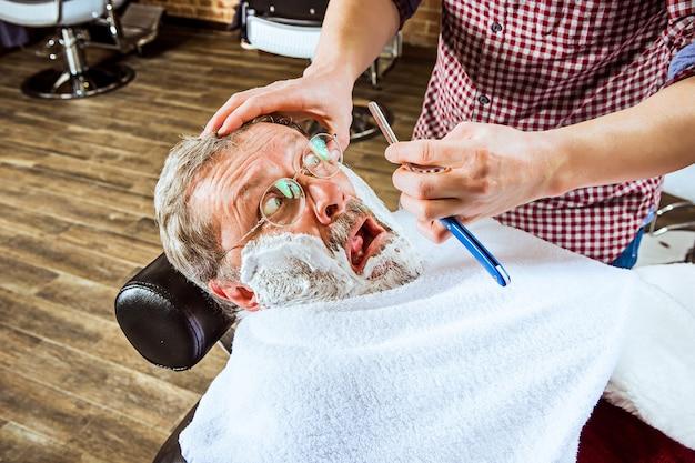 L'uomo anziano emotivo in visita dal parrucchiere nel negozio di barbiere
