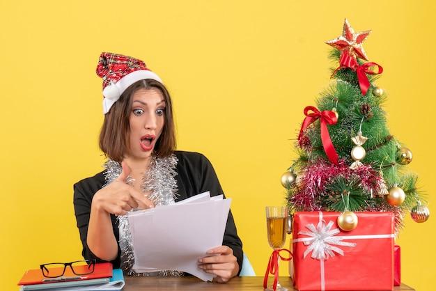 Donna d'affari scioccata emotiva in tuta con cappello di babbo natale e decorazioni di capodanno in possesso di documenti e seduta a un tavolo con un albero di natale su di esso in ufficio