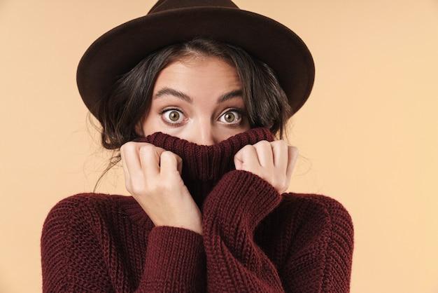 감정적으로 충격을 받은 젊은 브루네트 여성이 스웨터로 얼굴을 덮고 있는 베이지색 벽 벽 위에 고립된 채 포즈를 취했습니다.