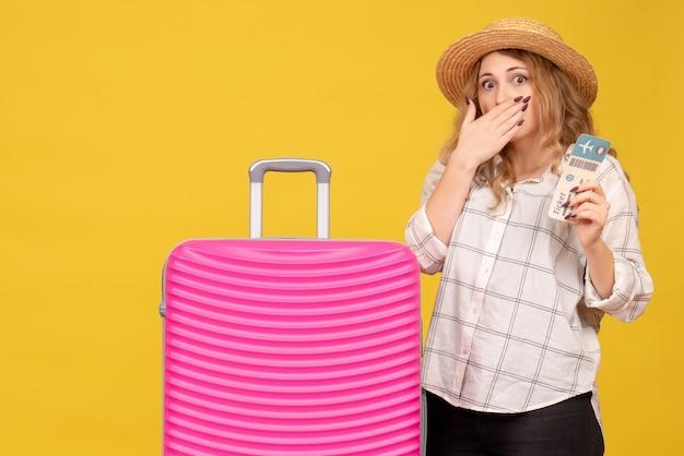 티켓을 보여주는 모자를 쓰고 그녀의 분홍색 가방 근처에 서있는 감정적 인 충격을받은 젊은 아가씨