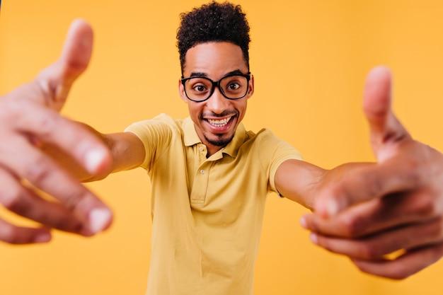 손을 흔들고 정서적 똑똑한 남자. 안경에 잘 생긴 갈색 머리 남자의 실내 사진.