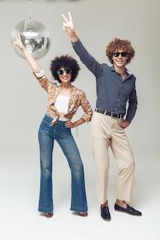Эмоциональное улыбается ретро влюбленная пара танцует возле диско-шар.