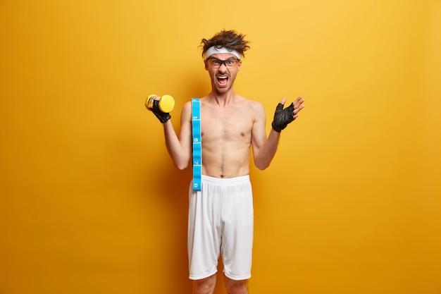 感情的なスポーツマンは、重いダンベルを持ち上げ、感情的に叫び、巻尺を持ち、スポーツグローブを着用し、健康的なライフスタイルを導き、黄色い壁に向かってポーズをとります。ボディケア、スポーツ、ダイエットのコンセプト