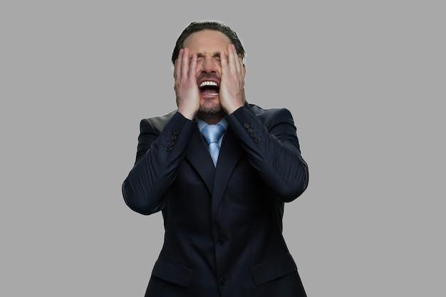 感情的なストレスのビジネスマンがクローズアップ。手で顔を覆っている絶望的な落ち込んでいるビジネスマン。絶望の表情。