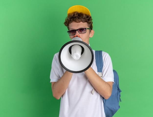 緑の背景の上に立っているメガホンに叫んでバックパックと眼鏡をかけている白いポロシャツと黄色の帽子の感情的な学生の男