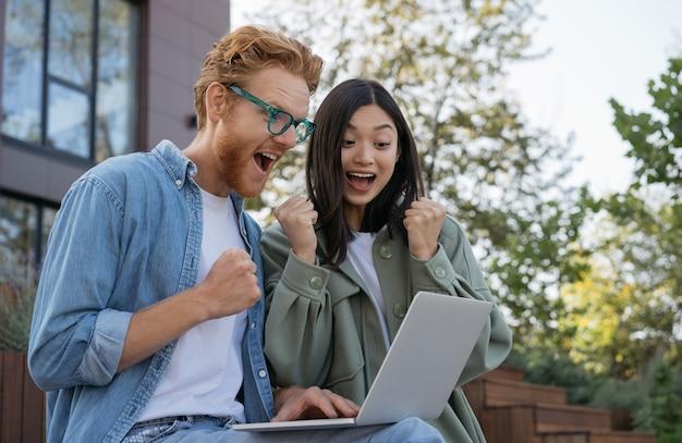 屋外に座って良いニュースのお祝いの成功を読んで感情的な学生