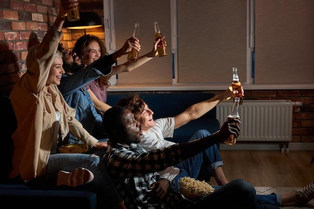 Эмоциональные студенты смотрят спортивный матч дома, сидя на диване. болельщики болеют за любимую американскую сборную, пьют пиво и едят попкорн. понятие эмоций, поддержки.