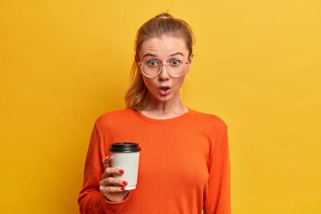 Una studentessa impressionata e stupefatta fa una pausa caffè, tiene una tazza di cappuccino usa e getta, indossa grandi bicchieri trasparenti, maglione arancione, ascolta nuovi pettegolezzi sul compagno di gruppo, beve bevanda caffeina