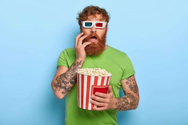 Uomo dai capelli rossi stupefatto emotivo fissa la telecamera attraverso gli occhiali del cinema