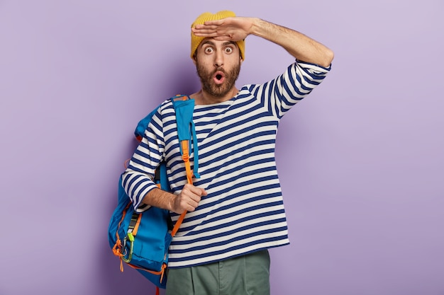 감정적 인 멍청한 청년은 무언가를 믿을 수 없으며 손바닥을 이마 근처에 두며 노란 모자와 줄무늬 점퍼를 착용합니다.