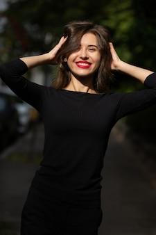 夏に通りを歩く古典的な黒い服を着た感情的なスタイリッシュな女性