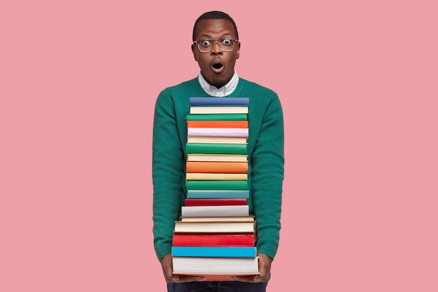 Emotional surprised black man looks with terrified expression, carries pile of textbooks, afraids of having many tasks to prepare, models over pink background