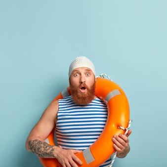 감정적 인 놀란 푸른 눈 수염을 가진 남성 휴가객, 해변에서 재현하고 입을 벌리고 폭풍에 충격을 받았습니다.