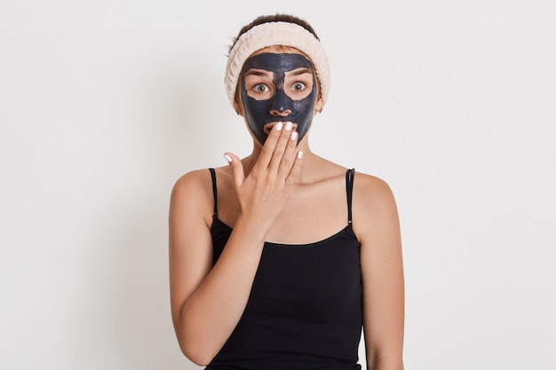 Emotional surprised caucasian woman looks with shocked expression, stands against white wall, cleans her skin with mud cosmetic mask.