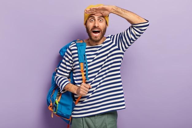 감정적 인 놀란 쾌활한 젊은 남성 관광객은 줄무늬 스웨터를 입은 이마 근처에 손바닥을 유지하고 개인적인 물건으로 파란색 배낭을 운반합니다.