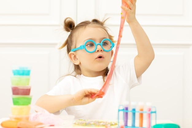 Эмоционально удивленный ребенок делает слизь в забавных очках