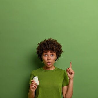La giovane donna riccia sorpresa emotiva punta il dito indice verso l'alto, mostra qualcosa di incredibile sopra, posa con lo yogurt, ha una corretta alimentazione, mantiene una dieta sana, vestita con una maglietta verde vivida
