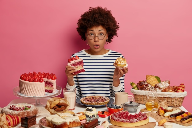 Emotional surprised dark skinned woman eats cake and cupcake, surrounded by tasty homemade desserts, has unhealthy nutrition, cannot believe something