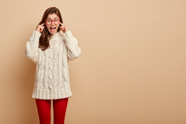 Emotional surprised female comes on loud party, dissatisfied with music, plugs ears, avoids noise, shouts to stop, wears casual sweater, red tights, poses over beige wall. omg its too noisy here