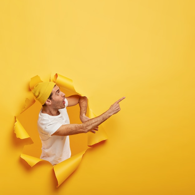 Emotional surprised guy stands in paper hole with ripped yellow edges, demonstrates incredible copy space
