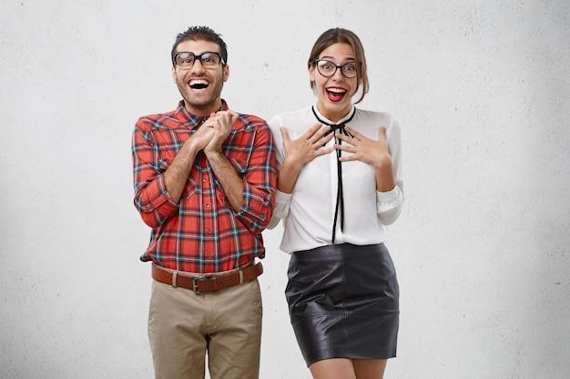 感情的に驚いた幸せな女と男は眼鏡をかけ、信じられないほどの表情を持っています