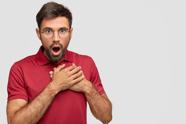 Emotional surprised male looks with bated breath, keeps mouth opened, terrific gaze can`t believe his eyes, wears casual red t-shirt, stands over white wall with blank copy space for text
