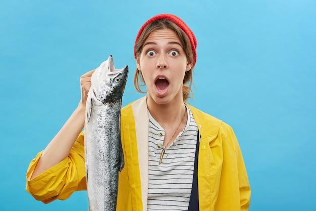 Emotiva sorpresa giovane pescatrice che indossa un impermeabile giallo e cappello che tiene un grosso pesce in mano e guarda con la bocca spalancata, scioccata dalla cattura fine. concetto di pesca