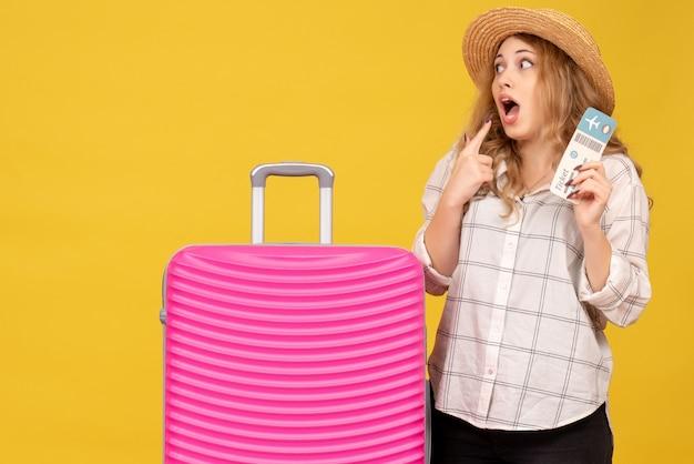 Эмоционально удивленная молодая дама в шляпе показывает билет и стоит рядом со своей розовой сумкой