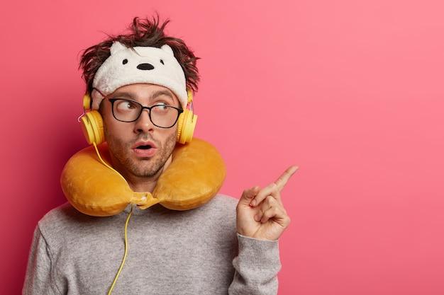 Эмоционально удивленный молодой человек слушает музыку в самолете