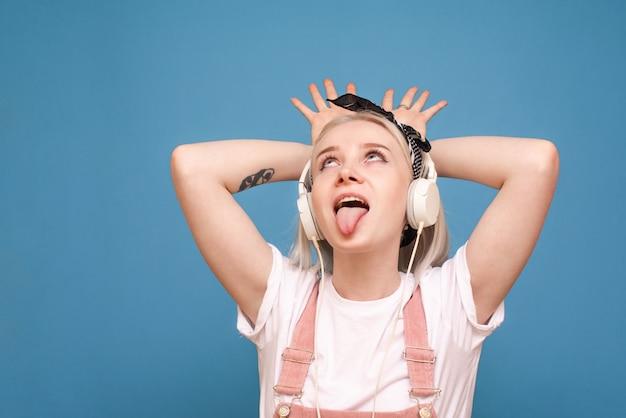 파란색 배경에서 음악을 듣고 감정적 인 십 대 소녀.