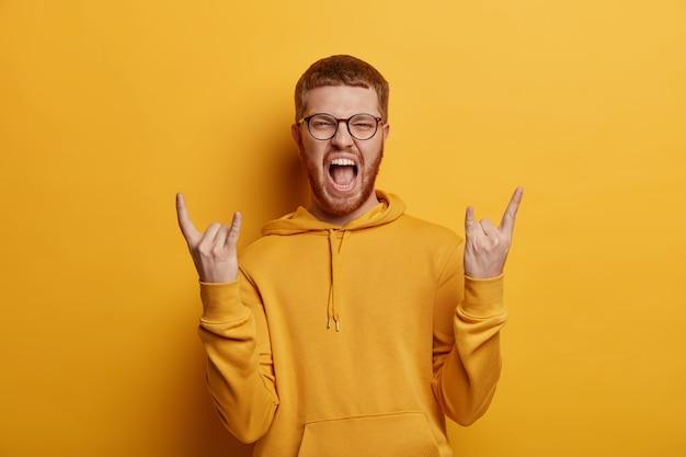 L'adolescente emotivo eccita di gioia, fa il gesto del rock n roll, porta vibrazioni positive, gode di un concerto fantastico, ascolta la musica preferita, vestito con una felpa, isolato su un muro giallo. linguaggio del corpo
