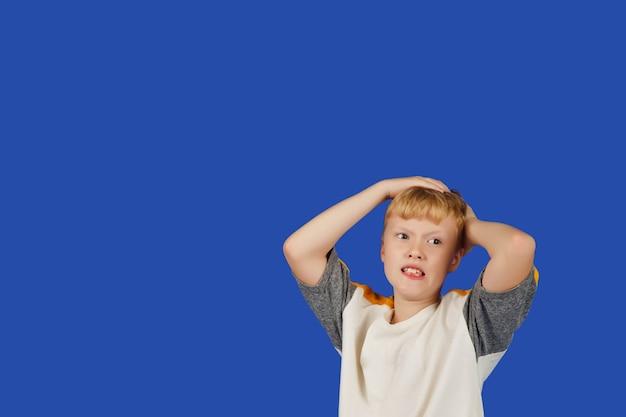 感情的なティーンエイジャーは、青いロイヤルの背景に対して孤立して、パニックで彼の頭を叫び、握りしめます。白いtシャツを着た白人の少年の肖像画。パニックになった男がカメラを見る。コピースペース