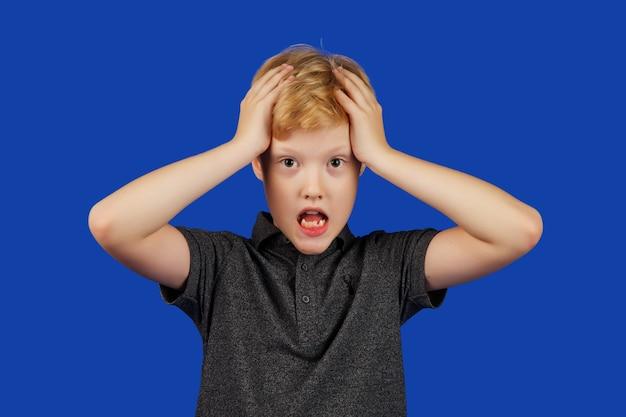 Эмоциональный подросток кричит и в панике хватается за голову