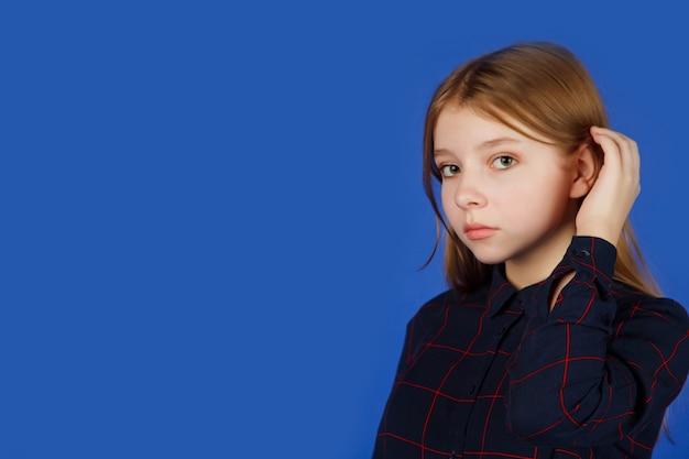 感情的な13歳のかわいい10代の少女は、青いロイヤルの背景に対して隔離されたカメラを注意深く見ています。黒い服を着た白人の子供が観客とイチャイチャします。コピースペース