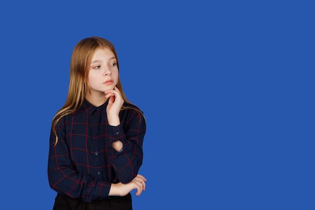 感情的な13歳のかわいい10代の少女は、青い王室の背景に対して隔離され、考えて目をそらします。黒い服を着た白人の子供は疑問符の感情を示しています。コピースペース