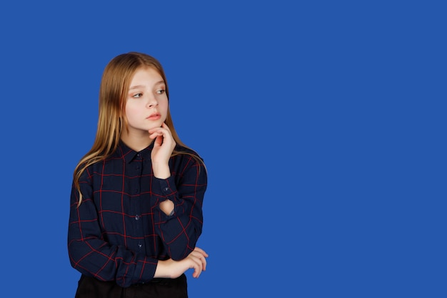 Emotional thirteen-year-old cute teenage girl thinking and looking away, isolated against blue royal background. caucasian child in black clothes shows question mark emotions. copy space
