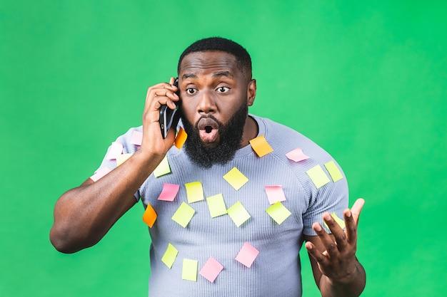Эмоциональный усталый афро-американский чернокожий мужчина подчеркнул, что из-за большой работы и крайнего срока разочарован изолированным на зеленом фоне. деловой человек. с помощью мобильного телефона.