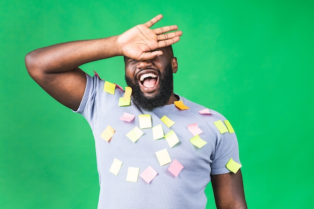 Эмоциональный усталый афро-американский чернокожий мужчина подчеркнул, что из-за большой работы и крайнего срока разочарован изолированным на зеленом фоне. деловой человек.
