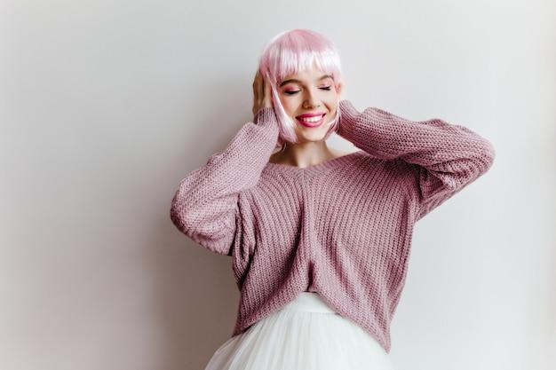 白い壁の前に立っている光沢のあるピンクの髪を持つ感情的なトレンディな女の子。 perukeと特大の紫色のセーターを着たのんきな女性の屋内写真。
