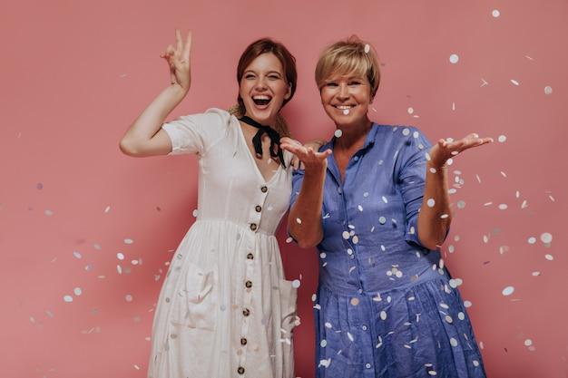Эмоциональные две дамы со стильной короткой прической в летней современной одежде смеются, показывают знак мира и позируют с конфетти на розовом фоне.