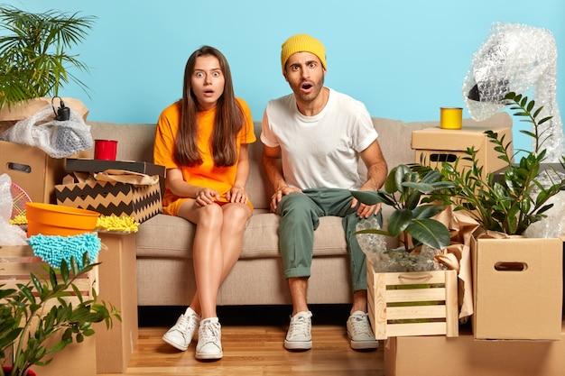 Эмоциональные две потрясенные женщина и мужчина смотрят с ошибочными глазами