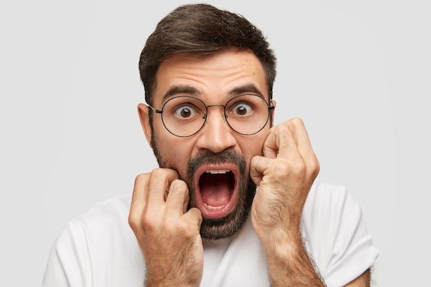 Un bell'uomo emotivo con la barba lunga urla ad alta voce, apre ampiamente la bocca, esclama stupefatto