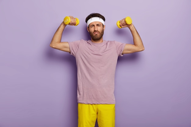 Emotional unshaven man being motivated to sport, leads healthy lifestyle, wants to have strong muscles, holds yellow dummbells, looks with tired expression, dressed in casual wear